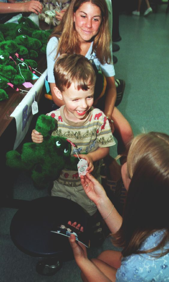 "Five-year-old Jacob Davis is all smiles after picking out a ""Belly Floppers"" frog at the Dodd Middle School Business Expo Tues., June 1, 1999 from Katie Olsen, bottom, and Meghan Ogurick, top. The products for sale by the students were all hand-made by them."