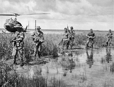 Members of a 9th Division Ranger unit,pause next to a bomb crater of Vietnam?s marshy unpopulated moonlike Plain of Reeds in the northwestern Mekong Delta, Vietnam on August 23, 1969, as a helicopter drops in to pick them up. (AP Photo/Ollie Noonan)