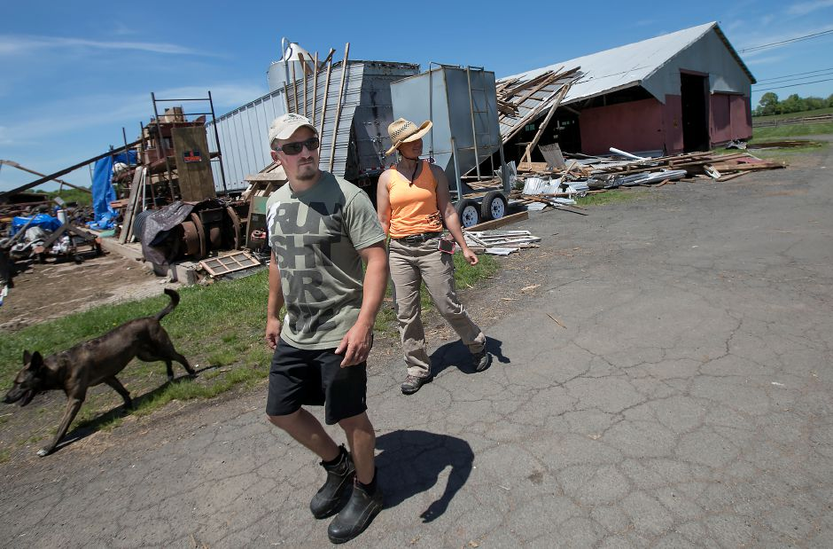 Wallingford farmers Chris Wellington and his wife, Kirsten Marra, walk past damage to barns on the Cooke family farm on Northford Road on Monday. Dave Zajac, Record-Journal