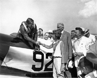 Jimmie Haizlip, new speed king of the national air races, tore into Cleveland at 238-mile-an hour clip on August 30, 1932 from New York. He is being greeted by Mrs. Amelia Earhart Putnam just after his arrival. Behind Mrs. Putnam is Senator Hiram Bingham of Connecticut. (AP Photo)