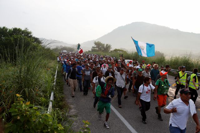 Migrants walk along the road after Mexico