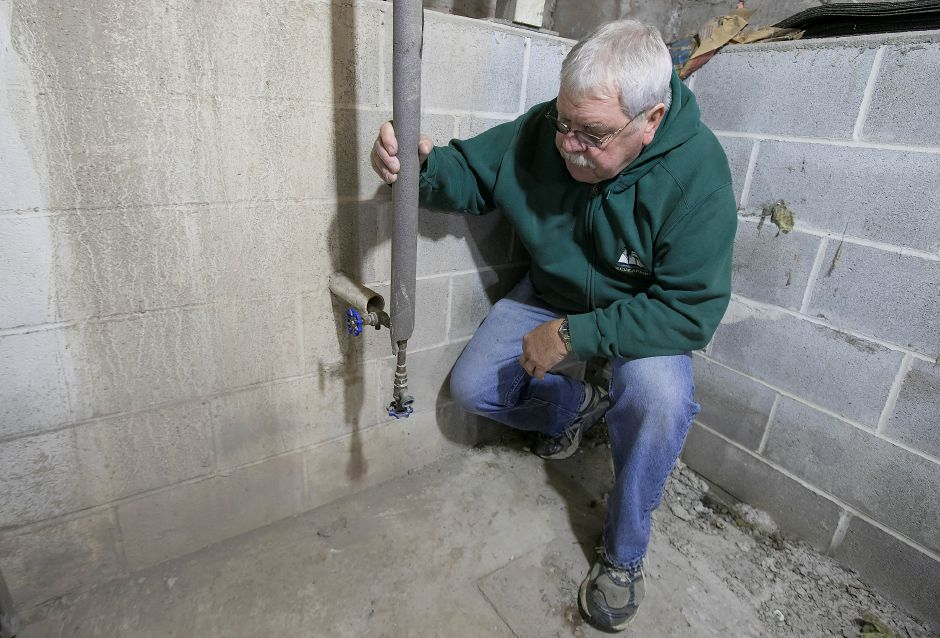 Larry Lacz, of Middlefield, shows the pipe where water enters his residence at 23 Lakeview Pl., Friday, Dec. 8, 2017. Lacz and several neighbors are concerned that their small privately owned water company, Rainbow Springs Water System, made a request to cease operations and abandon its water system. Neither the town nor other water utilities want to take over the Rainbow Springs system. Dave Zajac, Record-Journal