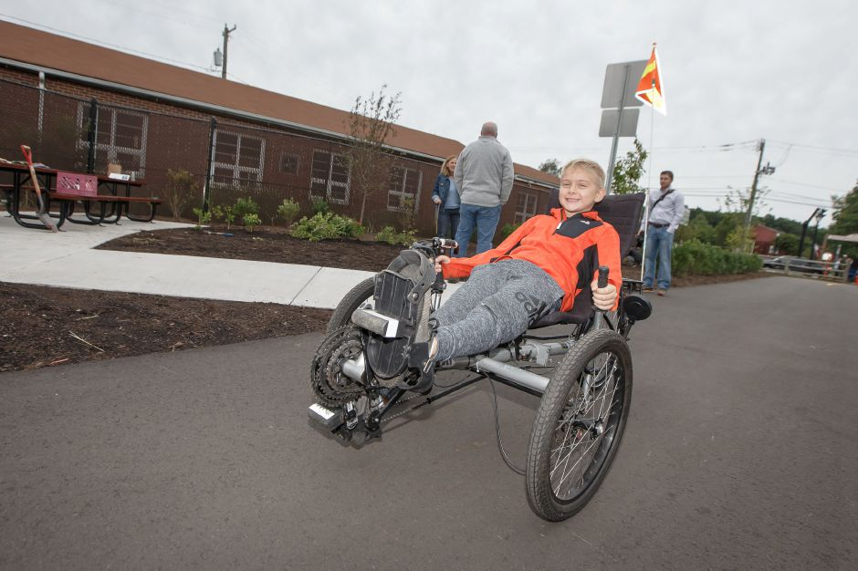 Eli Weed 7 of Cheshire tries out a tricycle Sunday during a Ribbon Cutting Ceremony for the Farmington Canal Heritage Trail on West Main in Cheshire September 9, 2018 | Justin Weekes / Special to the Record-Journal
