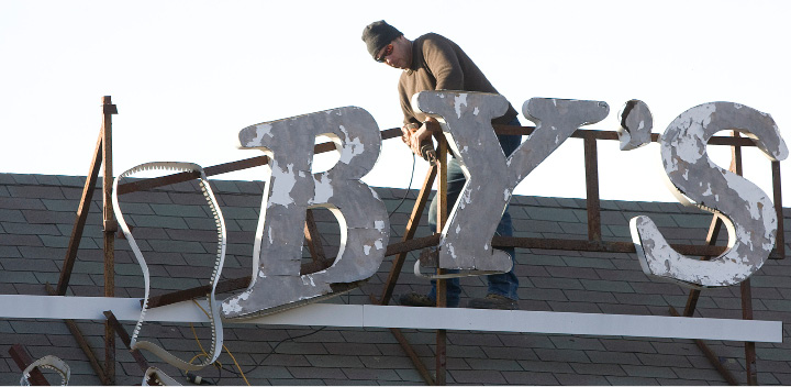 A worker cuts down lettering from the former Jacoby