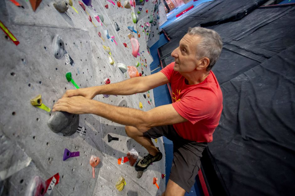 Brien Roscetti, owner of the Prime Club in Wallingford, looks for his next grip on the bouldering climbing wall. Richie Rathsack, Record-Journal