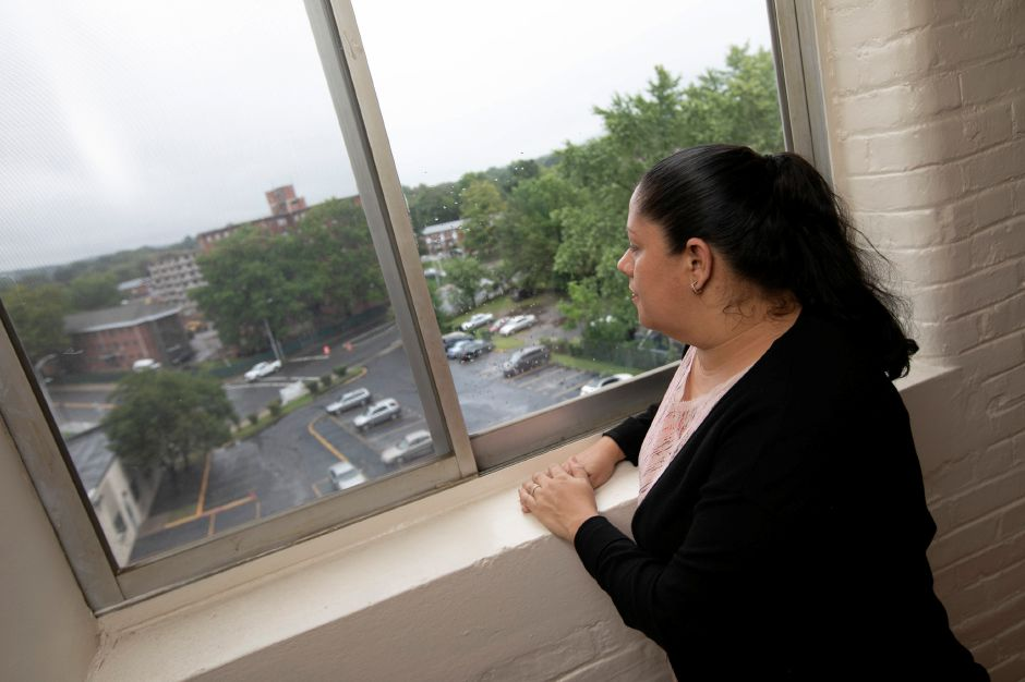 Johanna Roman, a bilingual tutor at Maloney High School, looks out over downtown Meriden from her residence, Wednesday, Sept. 12, 2018. Roman left her home in Arecibo, Puerto Rico due to Hurricane Maria. Dave Zajac, Record-Journal