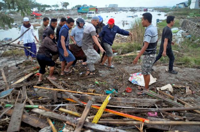 Residents carry a body bag containing the body of a tsunami victim in Palu, Central Sulawesi, Indonesia, Saturday, Sept. 29, 2018. A powerful earthquake rocked the Indonesian island of Sulawesi on Friday, triggering a 3-meter-tall (10-foot-tall) tsunami that an official said swept away houses in at least two cities. (AP Photo)