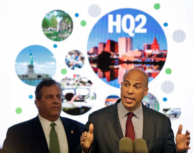 FILE - In this Monday, Oct. 16, 2017, file photo, New Jersey Sen. Cory Booker, right, speaks while New Jersey Gov. Chris Christie stands behind him during an announcement in Newark, N.J. New Jersey lawmakers have signed off on 5 billion in tax breaks to Amazon in an effort to convince the company that Newark would be the best location for the company