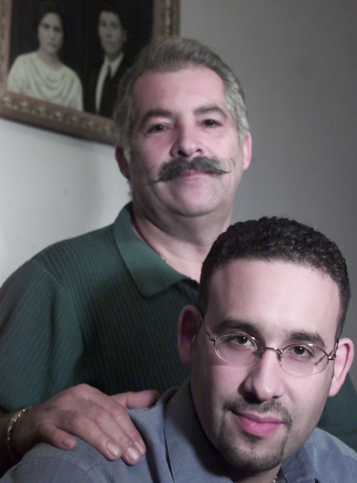 Hector Cardona Sr. and son Miguel Cardona. Behind them is a photo of Hector Cardona Sr.