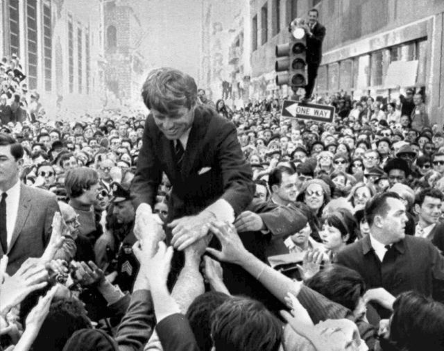 FILE - In this April 2, 1968 file photo U.S. Sen. Robert F. Kennedy, D-NY, shakes hands with people in a crowd while campaigning for the Democratic party