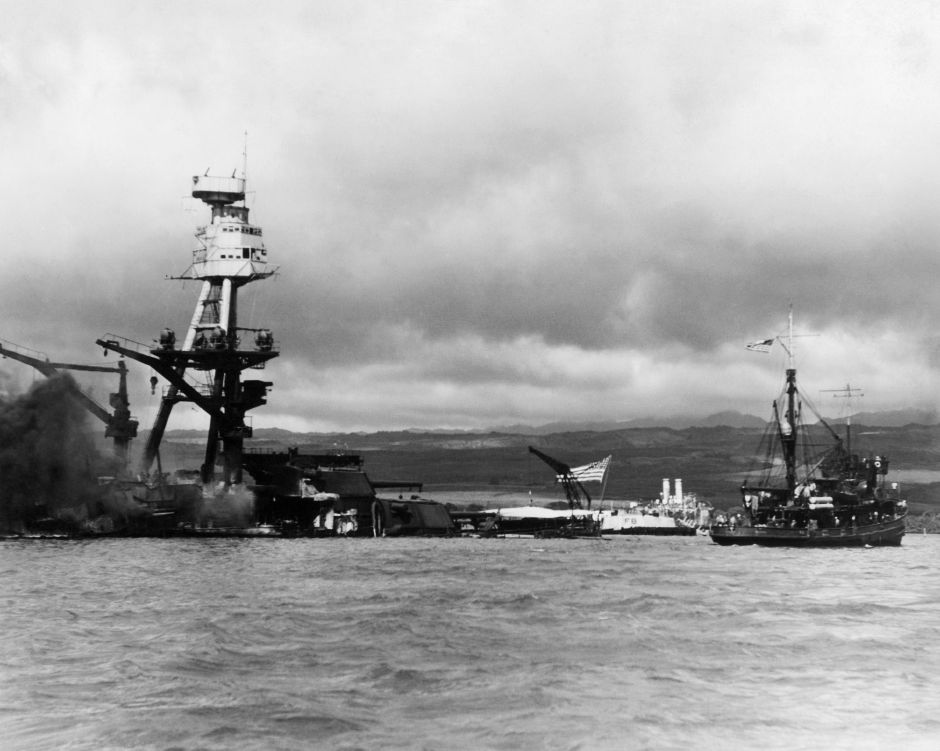 Battle ship Arizona at pearl Harbor, December 1941. The photo was taken shortley after the battleship was bombed and destroyed during the surprise attack by Japanese forces, December 7, 1941. The vessel at right is a rescue tug. Flag still flying the ship is resting on the bottom of the ocean with decks flooded. (AP Photo)