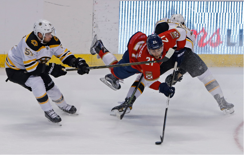 Florida Panthers center Vincent Trocheck (21) is upended by Boston Bruins defenseman Colin Miller (6) as Boston Bruins center Ryan Spooner (51) approaches in the second period of an NHL hockey game, Thursday, Dec. 22, 2016, in Sunrise, Fla. (AP Photo/Joe Skipper)