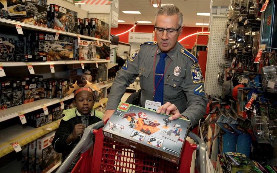 Above: State trooper Dave DeVito, of Wallingford, helps Daymian Rogers, 8, of Hartford, look for gifts during Shop with a Cop at Target in Southington on Thursday. The event was organized by the REACH Foundation. Bottom: Southington police officers Joe Vernali, left, and Jim Valentine, right, help Tazye Flemming, 11, of Southington, shop in the sporting goods section.