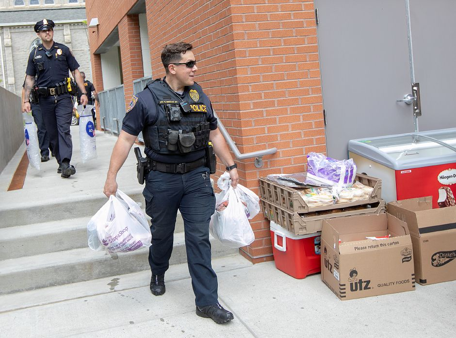 Ofc. Mike Shedlock carries food to a community cookout in the courtyard behind 24 Colony St. in Meriden, Fri., May 24, 2019. Downtown residents enjoyed a cookout with members of the police department and the NI unit as an ongoing effort to increase relationships between citizens and officers. Dave Zajac, Record-Journal