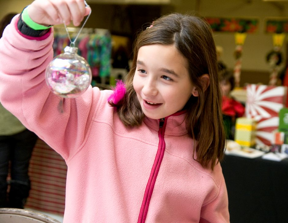 St. Joseph fourth grader Madison Whittle holds up a Christmas ornament she made during the St. Joseph Craft Fair in Meriden, December 2, 2011. (Sarah Nathan/Record-Journal)