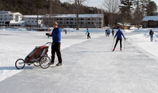 In this Jan. 20, 2018 photo, ice skaters travel passed the Lake Morey Resort, rear, on a 4.5-trail around Lake Morey in Fairlee, Vt., said to be the longest Nordic skating trail in the United States. (AP Photo/Lisa Rathke)
