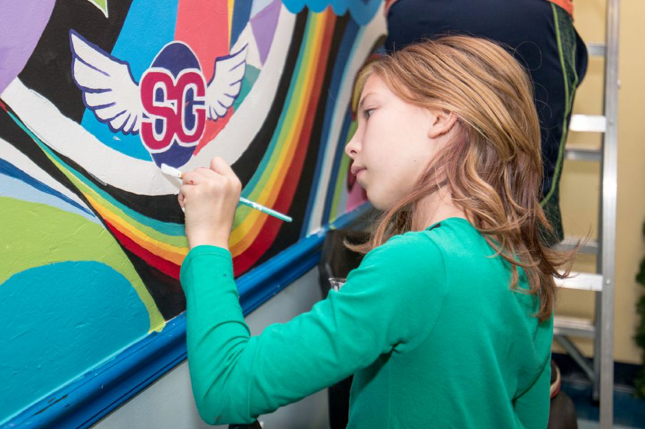 Madison Brauch, 10, paints in part of a rainbow in a mural being painted at the Ulbrich Boy