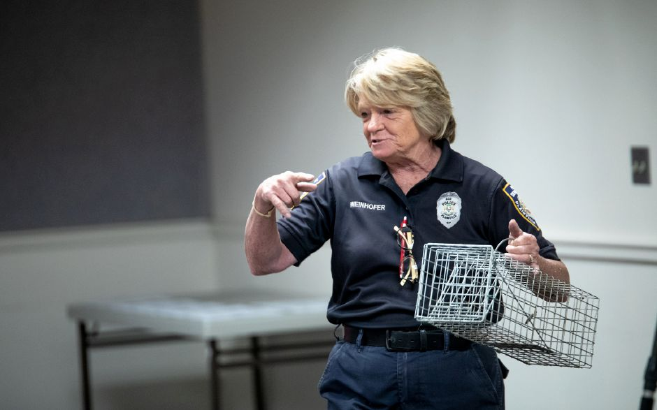 Plainville Animal Control Officer Donna Weinhofer shows a crowd of children one of her animal traps. Weinhofer visited the Plainville Public Library Tuesday night to help families understand the animals which live around them. | Devin Leith-Yessian / Plainville Citizen