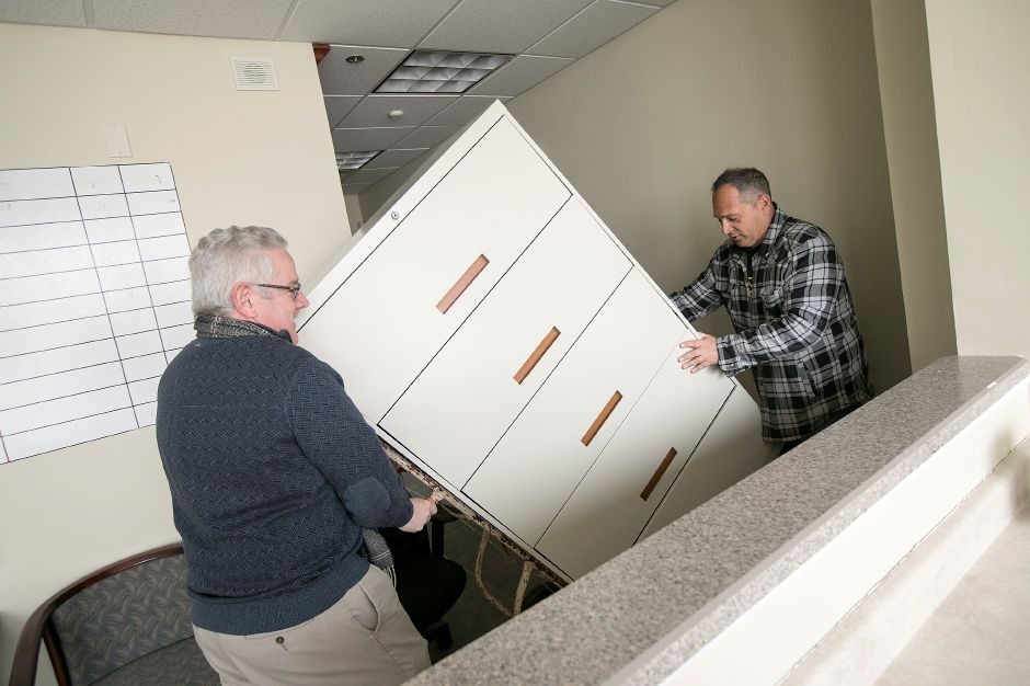 David Cooley, business consultant, left, and local developer Ross Gulino, move a filing cabinet into place while setting up the Meriden Economic Development Corporation's new office at 5 Colony St. in Meriden, Thursday, Feb. 1, 2018. Dave Zajac, Record-Journal