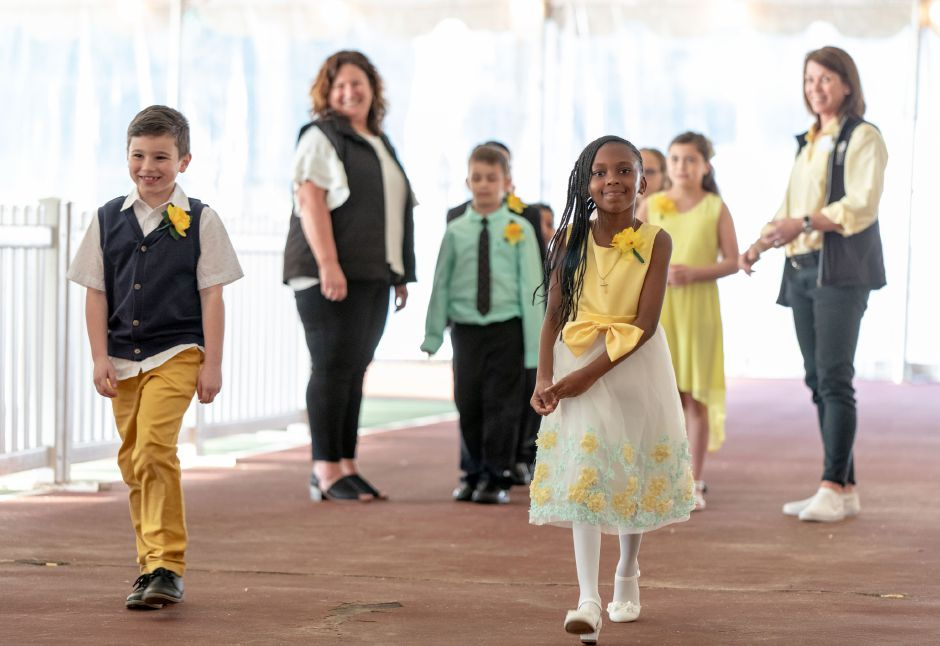 Gabrielle Merritt, 6, right, and Jayven Bergaynin, 7, of Nathan Hale Elementary School walk to the stage where Mayor Kevin Scarpati would crown on of the 9 girls there to be Miss Daffodil on April 24, 2019. The lucky elementary schooler will head the Meriden Daffodil Festival Parade on April 27. | Devin Leith-Yessian/Record-Journal