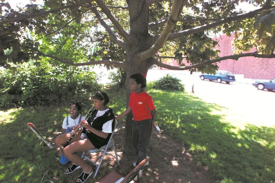 RJ file photo - In the shade of a tree, Hope Williams,9 (left) and her twin sister Fay Williams (right) hang out with Ashley Perry,13 (center) as she practices on her clarinet at the Faith Center Church on Crown Street, May 1999.