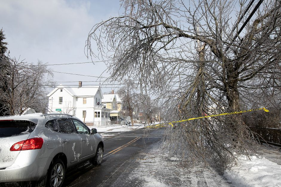 A vehicle travels past a fallen tree limb marked with caution tape on Washington Street in Wallingford, Mon. Jan. 21, 2019. Dave Zajac, Record-Journal