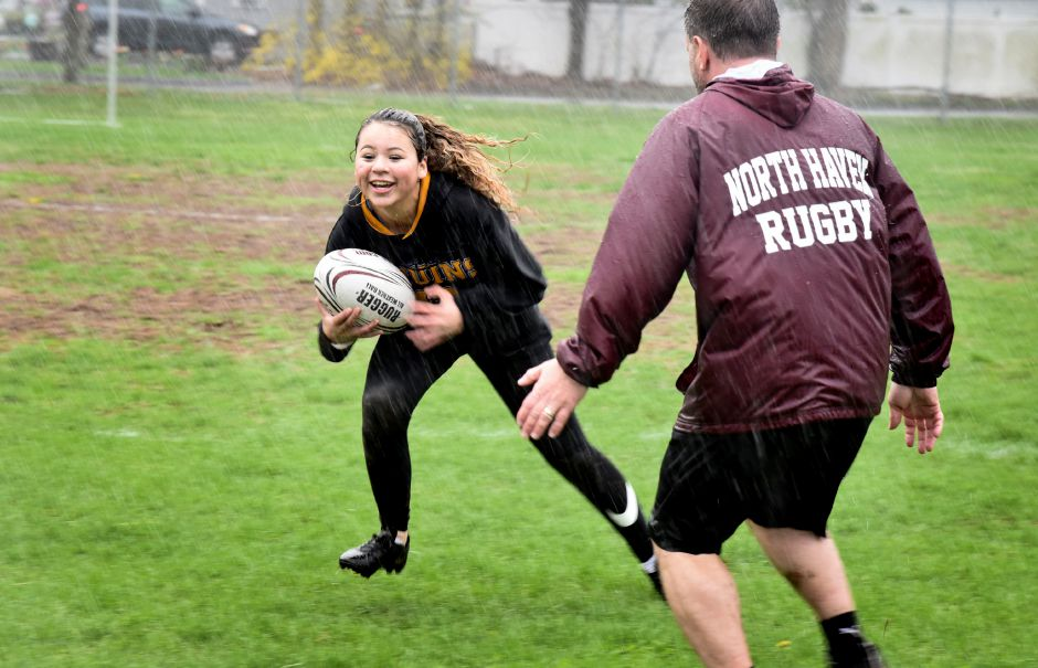 North Haven high school students practice rugby in the rain on Monday.
