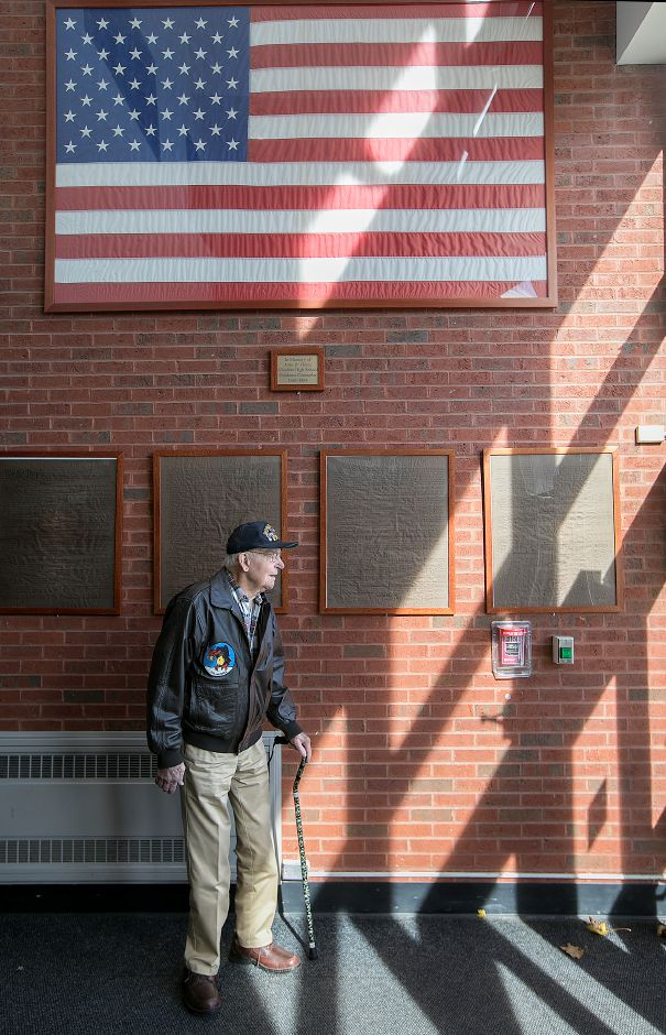 U.S. Air Force WWII veteran Irvin Daubert stands under the American flag after conclusion of a Veterans Day Celebration at Cheshire High School, Friday, Nov. 10, 2017. | Dave Zajac, Record-Journal