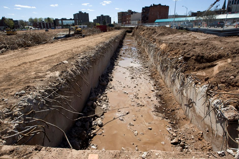 The exposed west culvert of Harbor Brook seen along State St. on the 14-acre Meriden Hub site Wednesday, April 29, 2015. Crews used a specialized steel cutting attachment for one of its backhoes that enabled them to snip through massive amounts of reinforced steel bars lining the culvert. | Dave Zajac / Record-Journal