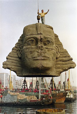 "In preparation for the opening of the Opera ""Aida,"" the 55-foot replica of the head of the Egyptian Sphinx is lowered into its platform on a boat in Kowloon Bay on Saturday, Sept. 21, 1991. The replica made of polyethylene will sail through Hong Kong harbor Sunday as part of a promotion of the opera's opening. (AP Photo/Vincent)"