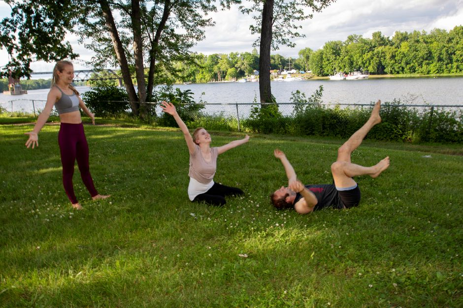 A little celebration after Christina Boyd and Sasha Krushnic taught Record-Journal Web Producer Ashley Kus the basics of Acro Yoga along the river in Middletown June 5, 2018. | Richie Rathsack, Record-Journal