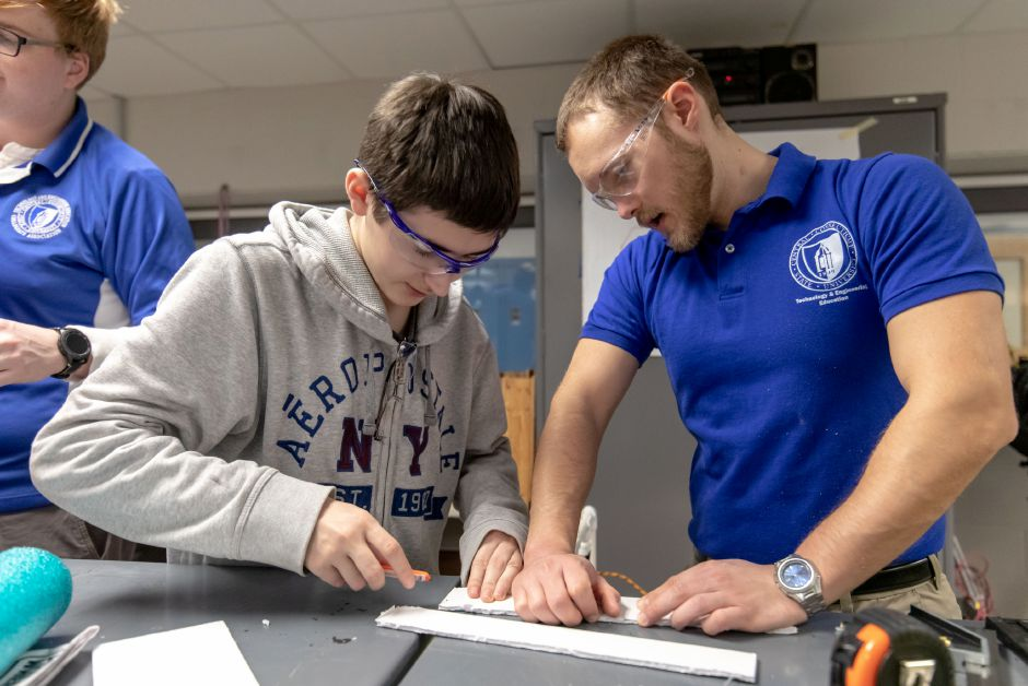 Kyle Guarco, left, and Gary Liseo cut styrofoam at Plainville High School. Central Connecticut State University students like Liseo helped local middle and high schoolers retrofit toy cars for children with limited mobility on Dec. 7 and 8, 2018. | Devin Leith-Yessian/Plainville Citizen