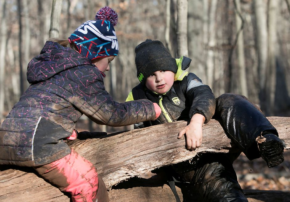 Moses Y. Beach Elementary School kindergarten students Lillian Gosztyla, 5, left, and Brian Choiniere, 5, climb around on a log during the Kinderwoods program at Kohler Environmental Center in Wallingford, Thursday, Dec. 7, 2017. Dave Zajac, Record-Journal