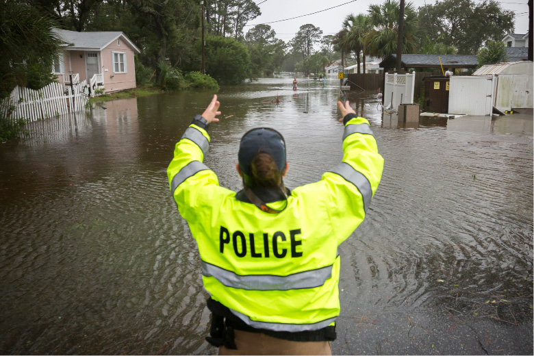 A City of Tybee police officer checks the well being of a resident fleeing her flooded home on Tybee Island, Ga., Monday, Sept., 11, 2017. Parts of the coastal Georgia island suffered from Tropical Storm Irma. (AP Photo/Stephen B. Morton)