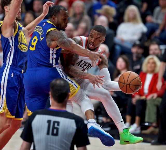 Portland Trail Blazers guard Damian Lillard, right, passes the ball away from Golden State Warriors guard Andre Iguodala, center, and guard Klay Thompson, left, during the first half of Game 3 of the NBA basketball playoffs Western Conference finals Saturday, May 18, 2019, in Portland, Ore. (AP Photo/Craig Mitchelldyer)