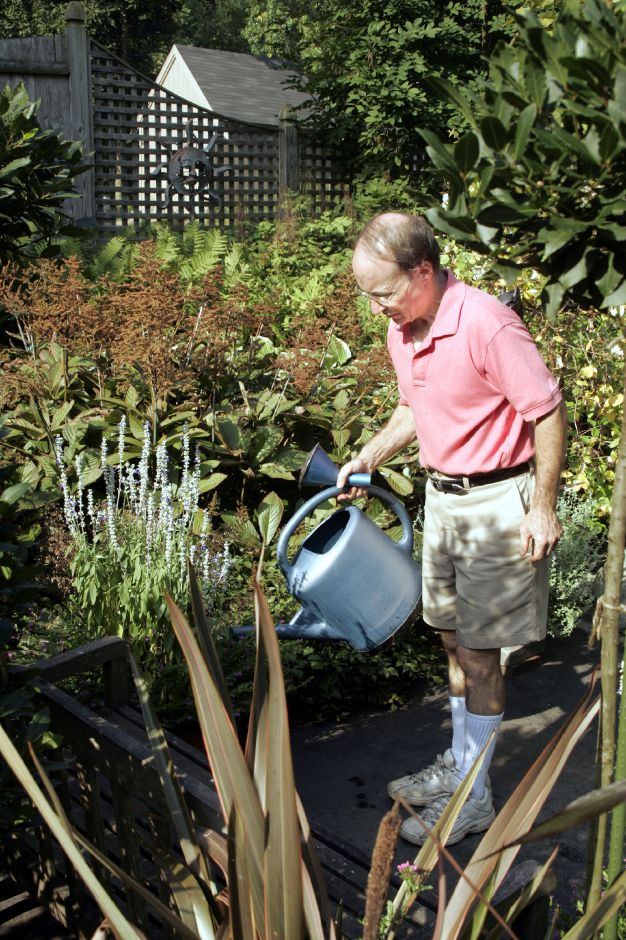 George Trecina waters some plants in his garden Wed., Sept. 14.