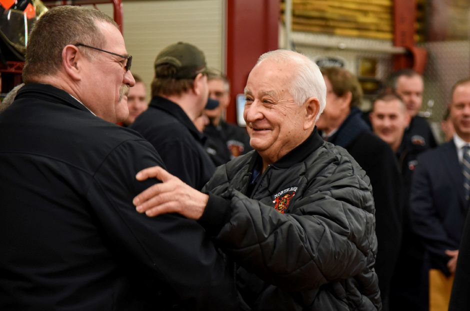 Joe DaCunto greets Wallingford Fire Chief Richard Heidgerd as he arrives at a surprise retirement party  at the North Farms Volunteer Fire Department on Monday. Bailey Wright, Record-Journal