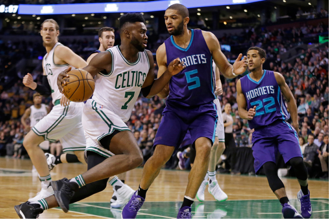 Boston Celtics forward Jaylen Brown (7) drives against Charlotte Hornets guards Nicolas Batum (5) and Brian Roberts (22) in the first quarter of an NBA basketball game, Friday, Dec. 16, 2016, in Boston. (AP Photo/Elise Amendola)