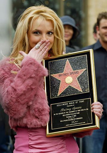 Pop star Britney Spears reacts to the screaming crowd as she holds up the plaque commemorating her new star on the Hollywood Walk of Fame, Monday, Nov. 17, 2003, in Los Angeles. Spears was honored with the 2,242nd star on the walk. (AP Photo/Nam Y. Huh)