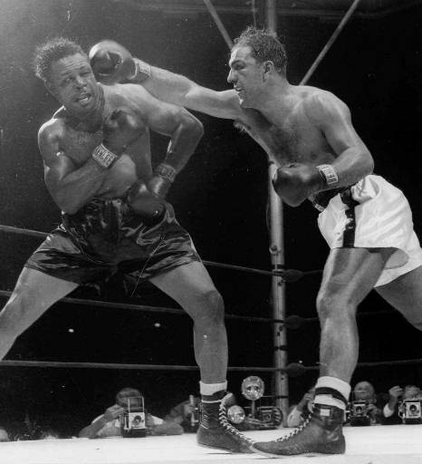 World heavyweight champion Rocky Marciano, delivers a right, that was followed by a left, that sent challenger Archie Moore, left, to the canvas for the full count in the ninth round of their 15-round title bout, Sept. 21, 1955 at Yankee Stadium in New York. (AP Photo)
