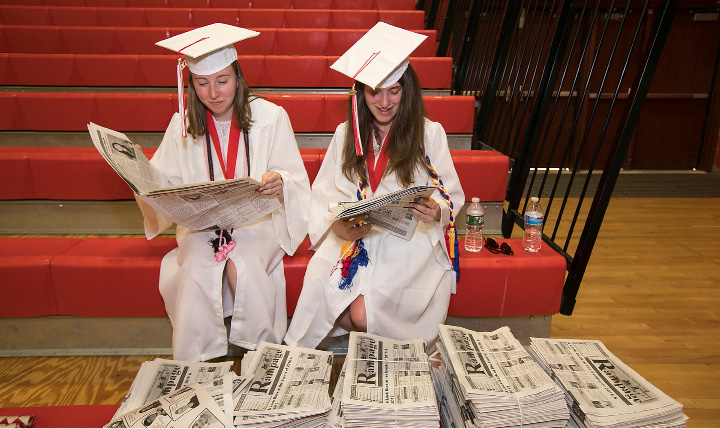 Graduates Elise Bowman, left, and friend, Samantha Korittke read copies of Rampage, the school newspaper, before graduation ceremonies at Cheshire High School, Wednesday, June 14, 2017.  | Dave Zajac, Record-Journal