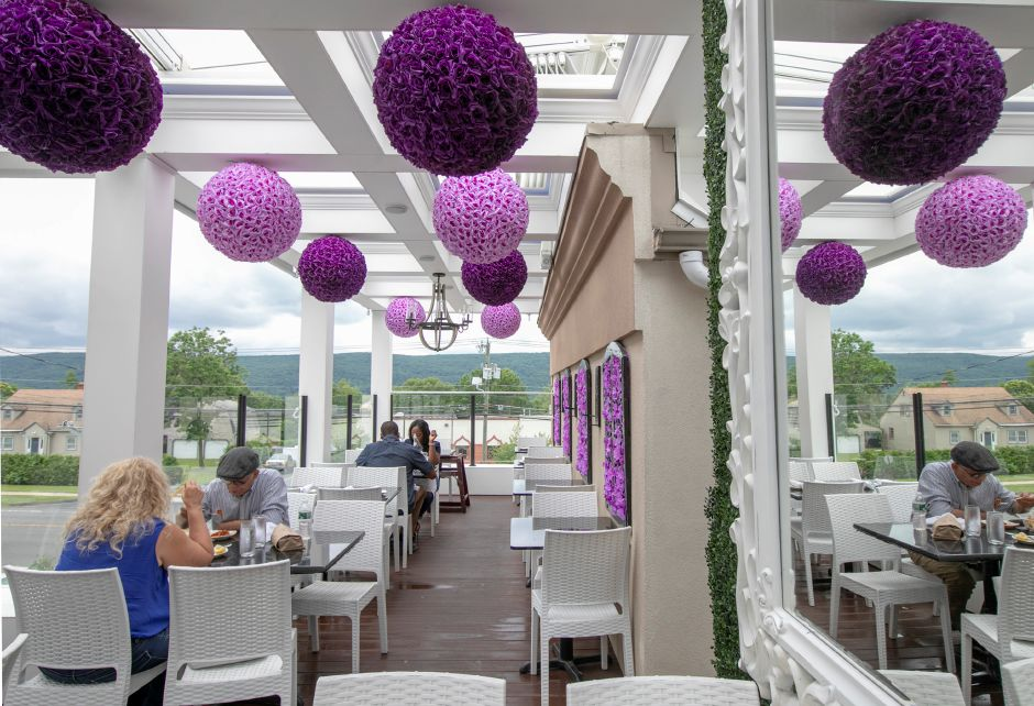 "Purple flower balls hang from the ceiling as part of the ""The Wizard of Oz""-themed rooftop dining at Cava Restaurant in Southington on Wednesday."