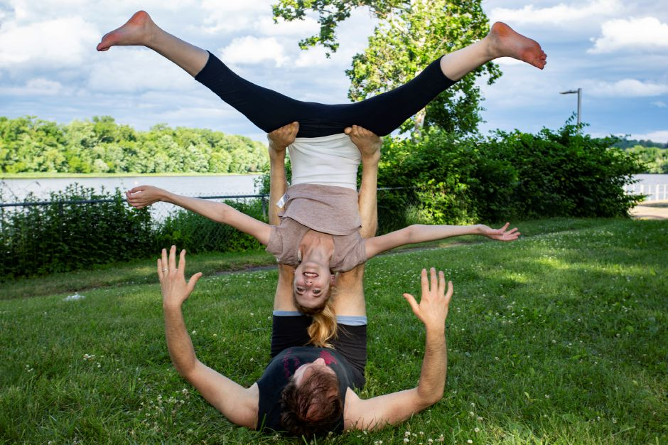Christina Boyd and Sasha Krushnic help Record-Journal Web Producer Ashley Kus try out Acro Yoga along the river in Middletown June 5, 2018. | Richie Rathsack, Record-Journal