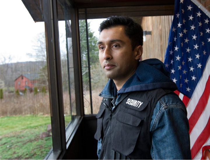 Adnan Shah, a member of the Ahmadiyya Muslim Community and part of their security personnel, stands in the entrance of the Baitul Aman Mosque in South Meriden before a prayer service, Friday, Dec. 18, 2015. Federal authorities have charged a city resident and former U.S. Marine living next door in the red house, left, with a hate crime after several shots were fired into the mosque, just hours after the terrorist attacks in Paris.  |  Dave Zajac / Record-Journal