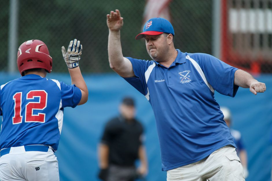 Simeon Levesque gets a high five from Wallingford head coach Brian Mitchell after hitting a pinch-hit, three-run homer in the third inning of Wednesday night's state Section 2 Little League All-Star game at Peter J. Foley Field in Naugatuck. | Justin Weekes / Special to the Record-Journal