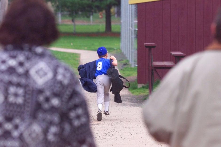 RJ file photo -Mary Ann Croce, left, follows her 8-year-old son Jonathan Croce as he runs eagerly toward his little league game at Keller Field in Yalesville, May 1999.