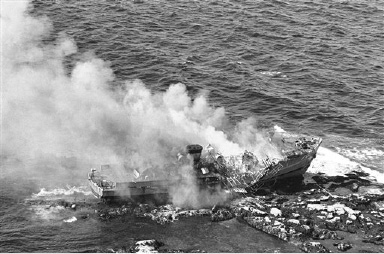 The 136-foot minesweeper Grouse, hard aground on a reef at the tip of Cape Ann off Rockport, Mass., burns up after the Navy set it on fire when several attempts to refloat her failed, Sept. 21, 1963. Thirty enlisted men and five officers were aboard when she went aground but all were removed safely. (AP Photo/J. Walter Green)