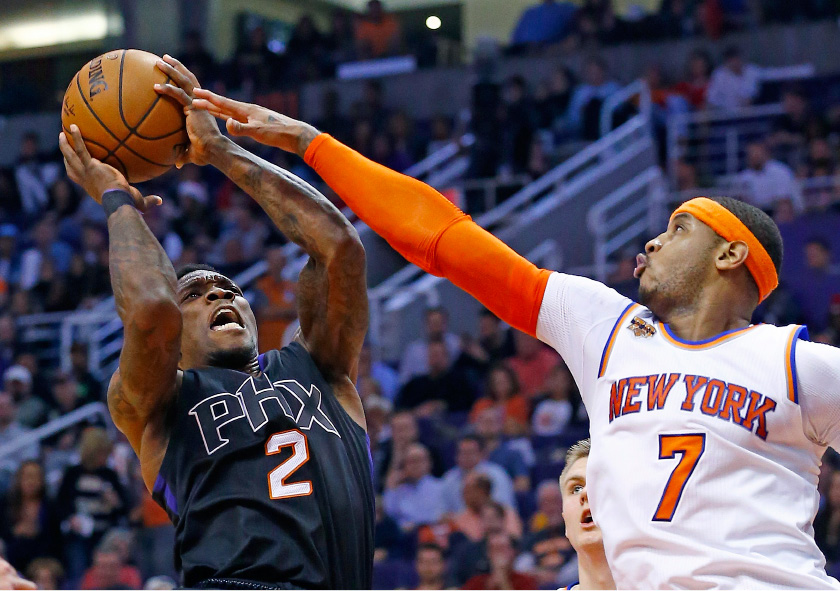 New York Knicks forward Carmelo Anthony (7) defends on a shot by Phoenix Suns guard Eric Bledsoe (2) during the second half of an NBA basketball game Tuesday, Dec. 13, 2016, in Phoenix. The Suns defeated the Knicks 113-111 in overtime. (AP Photo/Ross D. Franklin)