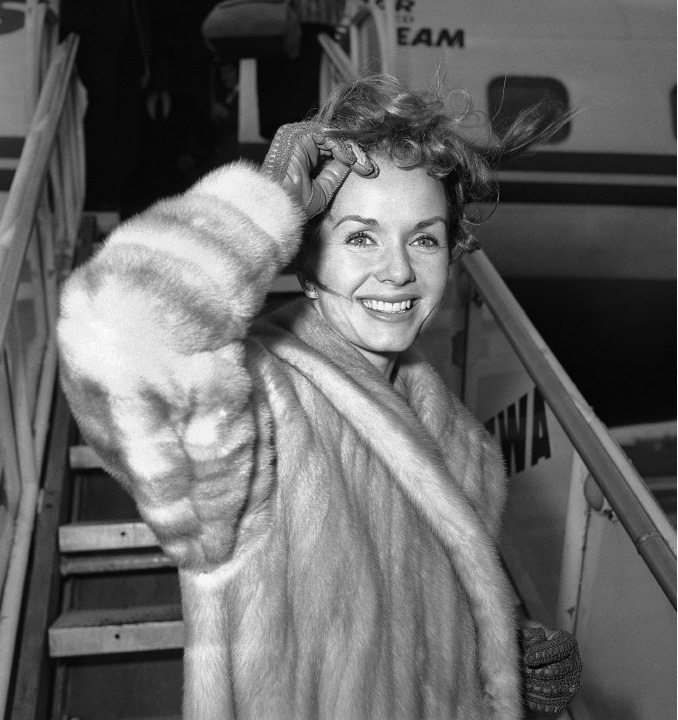 "FILE- In this March 6, 1959, file photo actress Debbie Reynolds boards an airliner in New York en route to Spain where she will film a new picture. Reynolds, star of the 1952 classic ""Singin"