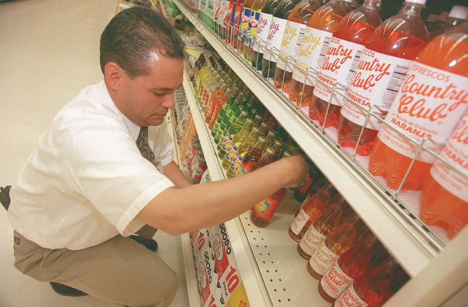 RJ file photo - Tony Perez, of Winthrop, Mass., stocks the shelves with Puerto Rican, Colombian and Jamaican soft drinks at the new Shaw